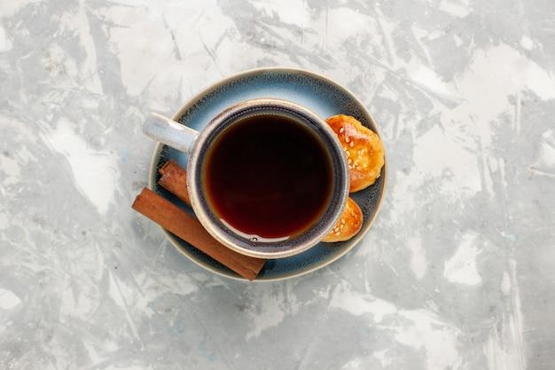 Bovenaanzicht kopje thee met kaneel en kleine cakes op witte ondergrond Gratis Foto