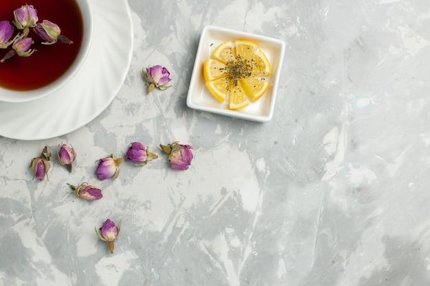Bovenaanzicht kopje thee met kleine bloemen op lichtwit bureau Gratis Foto