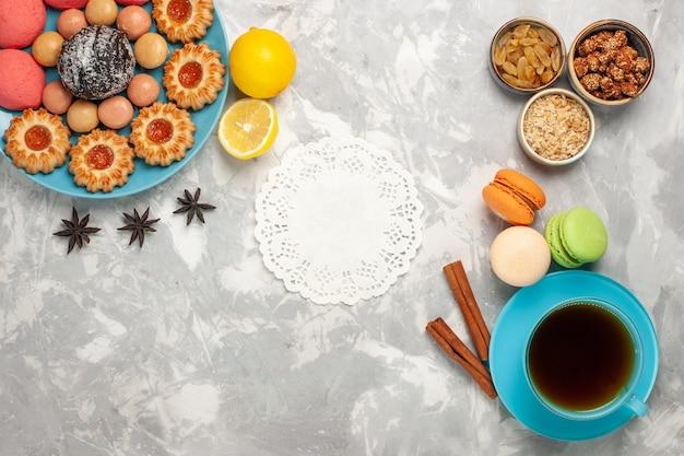 Bovenaanzicht kopje thee met koekjes en roze taarten op wit bureau Gratis Foto