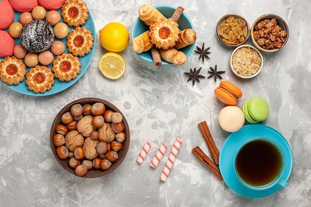 Bovenaanzicht kopje thee met koekjes, noten en roze taarten op witte ondergrond Gratis Foto
