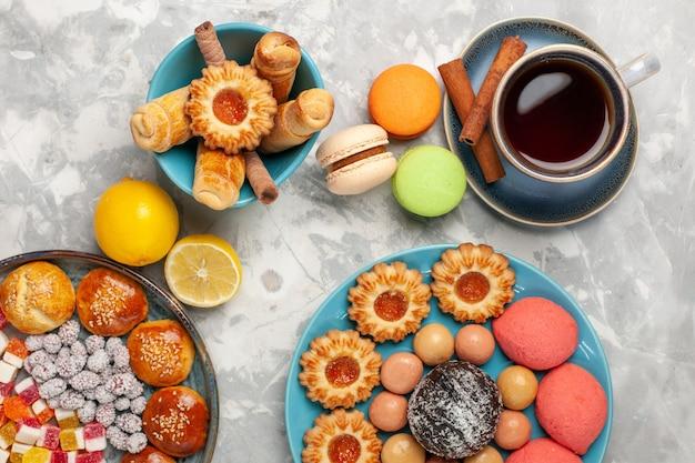 Bovenaanzicht kopje thee met taarten, koekjes en macarons op witte ondergrond Gratis Foto