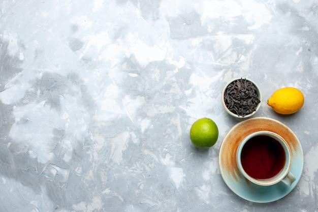 Bovenaanzicht kopje thee met verse citroenen en gedroogde thee op de lichttafel, thee fruit citrus kleur drankje Gratis Foto