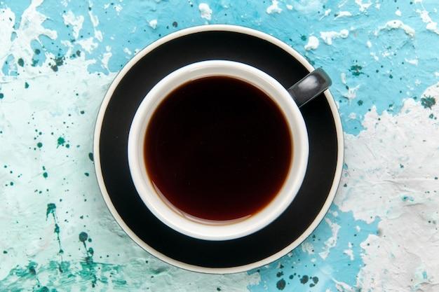 Bovenaanzicht kopje thee warme drank in plaat op lichtblauwe ondergrond Gratis Foto