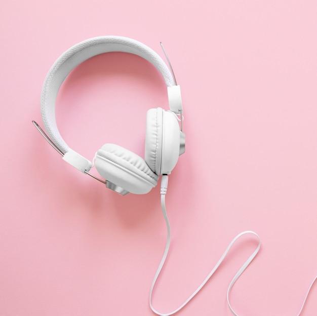 Bovenaanzicht koptelefoon op roze achtergrond Gratis Foto
