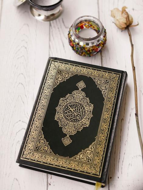 Bovenaanzicht koran en roos op tafel Gratis Foto