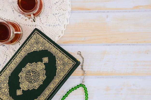Bovenaanzicht koran, thee en gebedskralen Gratis Foto