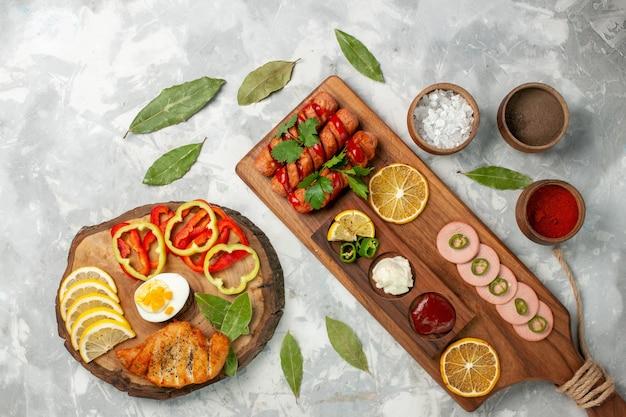 Bovenaanzicht kruiden en groenten met citroenen op licht wit bureau Gratis Foto