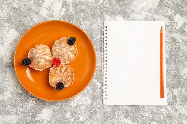 Bovenaanzicht lekkere deegcakes met suikerpoeder en blocnote op witte achtergrond Gratis Foto