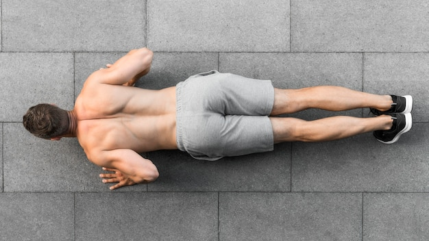 Bovenaanzicht man doet push-ups Premium Foto