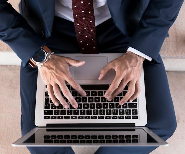 Bovenaanzicht man in pak die op laptop werkt Gratis Foto