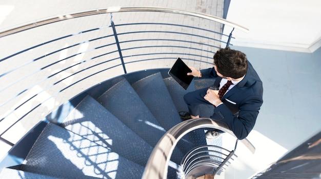 Bovenaanzicht man met tablet staande op trappen Gratis Foto