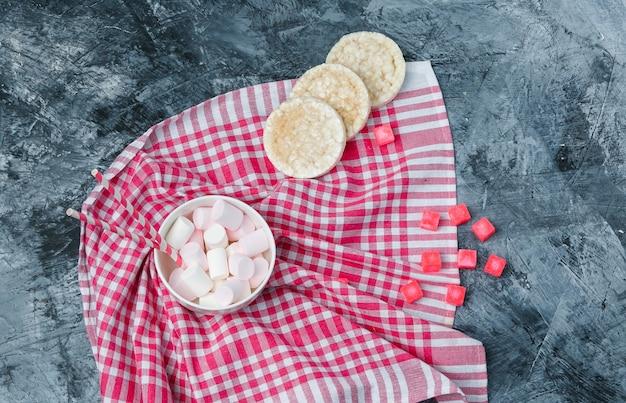 Bovenaanzicht marshmallows en suikerriet in beker met rijstwafels, snoepjes en rood geruit tafelkleed op donkerblauw marmeren oppervlak. horizontaal Gratis Foto