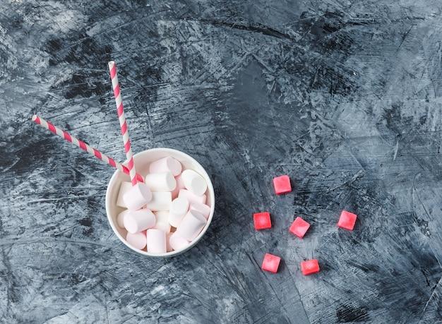 Bovenaanzicht marshmallows met suikerriet en rode snoepjes op donkerblauw marmeren oppervlak. horizontaal Gratis Foto
