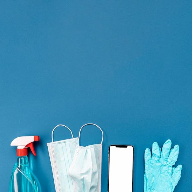 Bovenaanzicht medisch masker en handschoenen met lege telefoon Gratis Foto