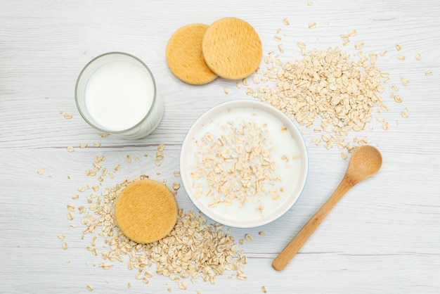 Bovenaanzicht melk met havermout samen met glas melk en koekjes op wit, zuivel melk ontbijt gezondheid Gratis Foto