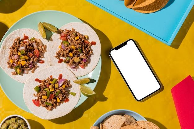 Bovenaanzicht mexicaans eten en smartphone Gratis Foto