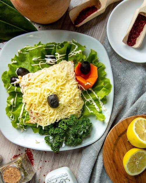 Bovenaanzicht mimosa salade op sla blad met olijven Gratis Foto