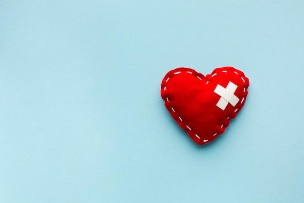 Bovenaanzicht minimalistisch rood hart op blauwe achtergrond Gratis Foto