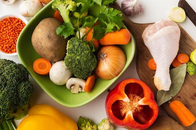 Bovenaanzicht mix van groenten op snijplank en in kom met kip drumstick Gratis Foto