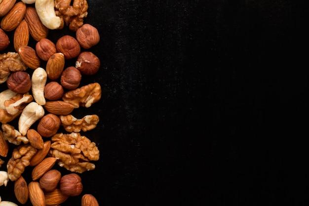Bovenaanzicht mix van noten frame op een zwarte tafel Premium Foto
