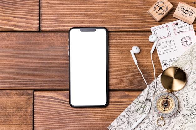 Bovenaanzicht mobiele telefoon met kompas en wereldkaart Premium Foto