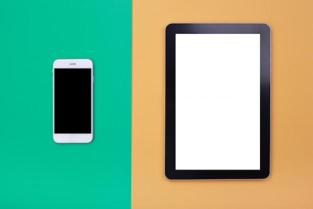 Bovenaanzicht mockup-tablet en smartphone op groene en oranje pastel achtergrond Premium Foto