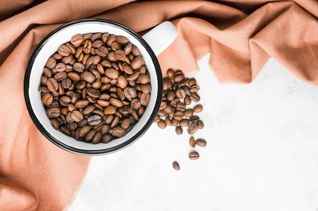 Bovenaanzicht mok met gebrande koffiebonen Gratis Foto