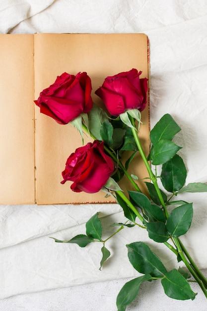 Bovenaanzicht mooie rode rozen op een boek Gratis Foto