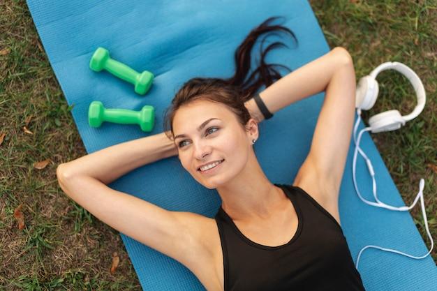 Bovenaanzicht mooie vrouw rusten op yoga tapijt Gratis Foto