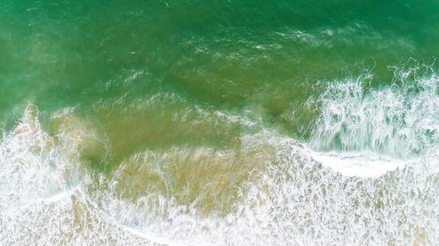 Bovenaanzicht natuur landschap van vloeiende golf witte seafoam turquoise golven prachtige tropische zee in zomer seizoen afbeelding door luchtfoto drone geschoten, hoge hoek bekijken top down. Premium Foto