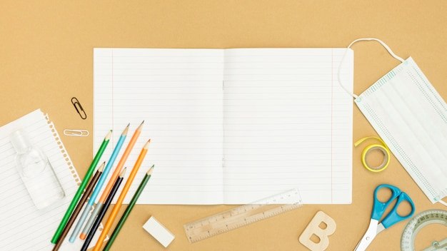 Bovenaanzicht notebook en potloden arrangement Gratis Foto