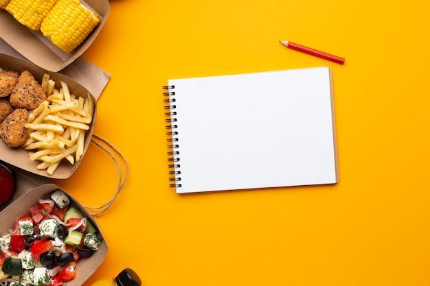 Bovenaanzicht notebook met voedsel op gele achtergrond Gratis Foto