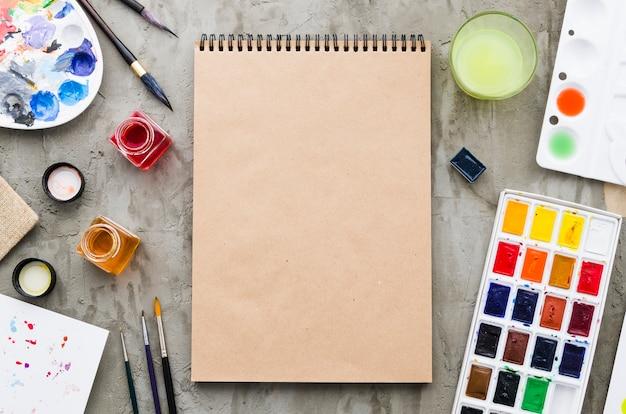 Bovenaanzicht notebook omgeven door elementen te schilderen Gratis Foto
