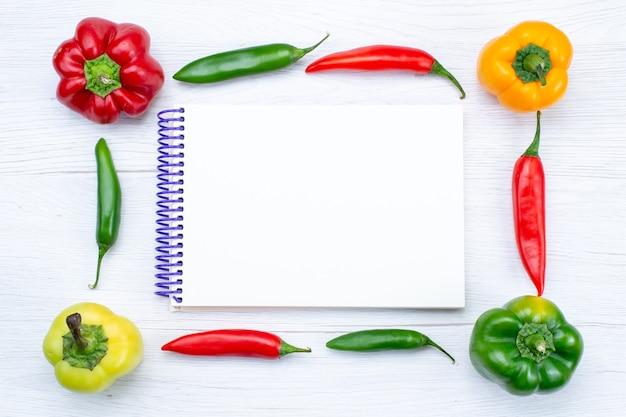 Bovenaanzicht offul paprika's bekleed met pittige paprika's en blocnote op wit, plantaardig kruid warm voedsel maaltijdproduct Gratis Foto