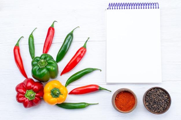 Bovenaanzicht offul paprika's met pittige paprika's blocnote kruiden op wit bureau, plantaardig kruid warm voedsel maaltijd ingrediënt product Gratis Foto