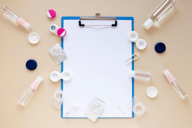 Bovenaanzicht oogverzorging accessoires op beige achtergrond met klembord mock-up Gratis Foto