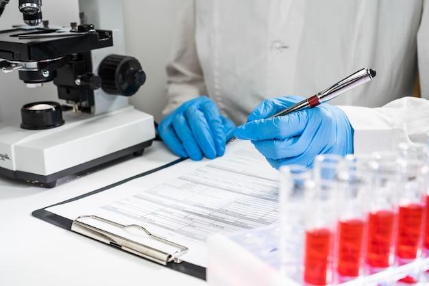 Bovenaanzicht op de werkplek van de arts. reageerbuizen met bloedonderzoeken, de arts schrijft de resultaten in het formulier Premium Foto