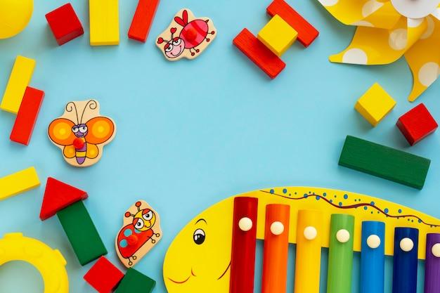 Bovenaanzicht op educatieve kinderen spelletjes, frame van veelkleurige kinderen houten speelgoed op lichtblauwe papier achtergrond. plat lag, kopieer ruimte voor tekst. Premium Foto