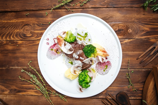 Bovenaanzicht op gastronomisch ingerichte schotel met rundvlees op de houten tafel Premium Foto