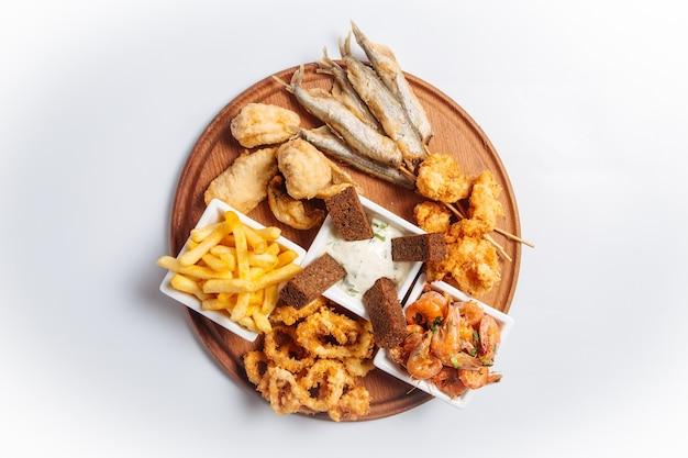 Bovenaanzicht op geïsoleerde gebakken schaal-en schelpdieren bier schotel met vis en garnalen op het houten bord Premium Foto