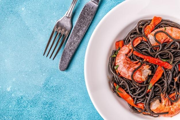 Bovenaanzicht op gekookte zwarte pasta met garnalen Premium Foto