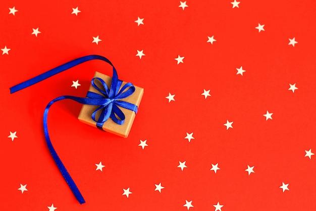 Bovenaanzicht op kerstcadeaus met lint op rode papier achtergrond met zilveren sterren Premium Foto