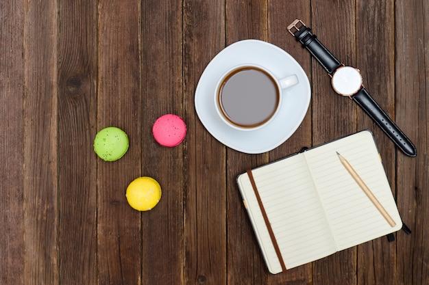 Bovenaanzicht op kopje koffie, macarons, laptop en horloge. Premium Foto