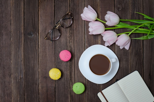 Bovenaanzicht op kopje thee, macarons, glazen, roze tulpen en laptop Premium Foto