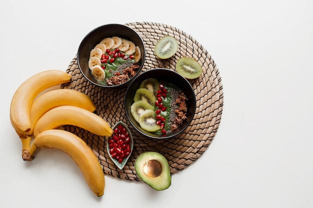 Bovenaanzicht op plaat van groene smoothiekom gegarneerd met avocado en spinazie, granaatappelpitjes en granola. Gratis Foto
