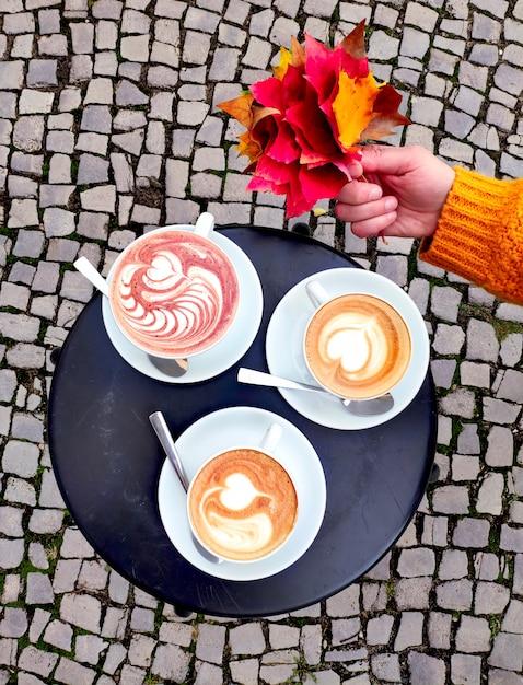 Bovenaanzicht op ronde metalen tafel buitenshuis met twee kopjes latte en kop warme chocolademelk. de straat met keien en dient saffraan gele sweater in houdend rode esdoornbladeren. Premium Foto