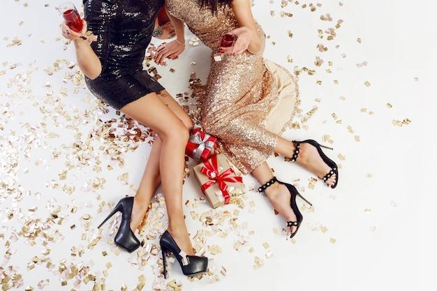 Bovenaanzicht op sexy vrouwen benen op achtergrond van glanzende gouden confetti, geschenkdozen, glazen champagne Gratis Foto