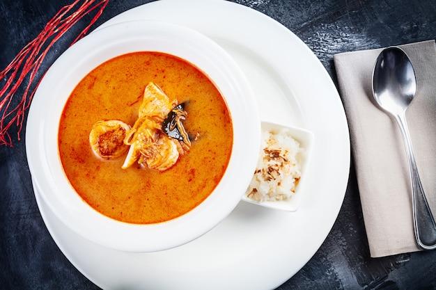 Bovenaanzicht op tom yum soep geserveerd in witte plaat met rijst. soep met garnalen, zeevruchten, kokosmelk en spaanse peper in kom kopie ruimte. traditionele thaise keuken. lunch eten met kopie ruimte Premium Foto
