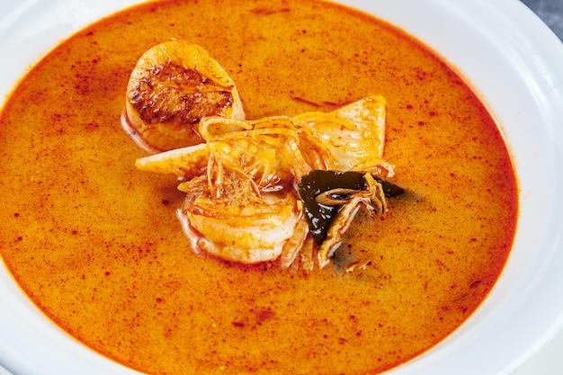 Bovenaanzicht op tom yum soep geserveerd in witte plaat met rijst Premium Foto
