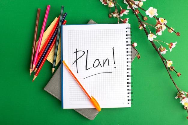 Bovenaanzicht open voorbeeldenboek met kleurrijke potloden en bloemen op het groene oppervlak Gratis Foto